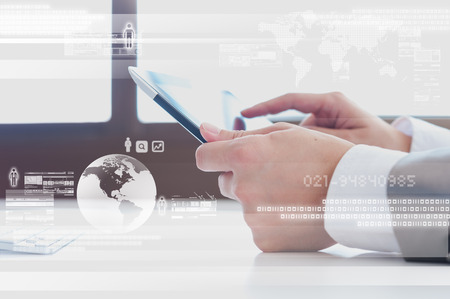 information international: Close up scene of Business man using tablet with digital layer effect Stock Photo