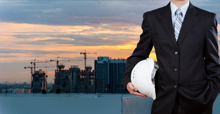 worker construction: Businessman holding safety helmet with city background