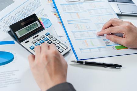 equities: Businessman using calculator analyze report