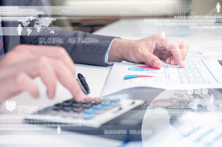 Business person using calculator against technology background photo