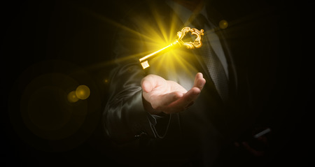 businessman hold a gold shining key, business concept Banco de Imagens