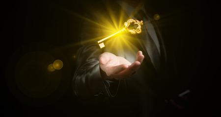 zaken man houdt een gouden glanzende sleutel, business concept Stockfoto