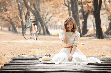 beautiful young woman sit on wooden bridge in park photo