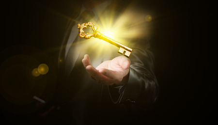 businessman hold a gold shining key, business concept Imagens