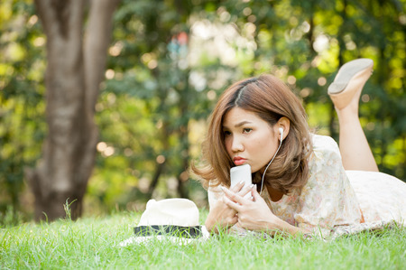 lia: Young woman lay on grass in park using smart phone Stock Photo