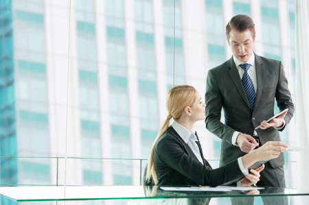 businessman and woman discussing in office photo