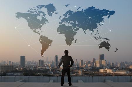 skyscrabber、ビジネスのグローバル化の概念の屋根の上に立つビジネスマン
