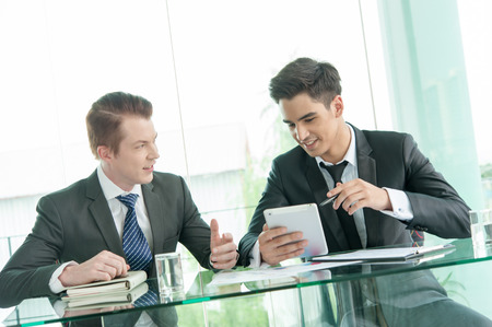 pointing device: Two businessman using tablet in meeting