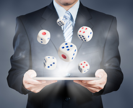 risks icon: Businessman using tablet showing dice, risk management concept Stock Photo