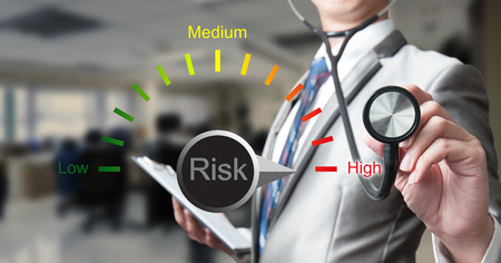 illness: Business man with stethoscope with risk management concept Stock Photo