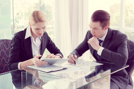 business suit: businessman and woman discussing in office Stock Photo