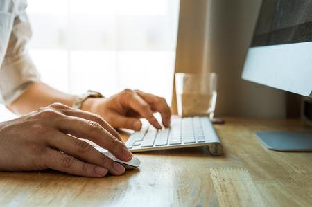 patron: Hombre que usa el ordenador de la PC de escritorio, el concepto de oficina móvil