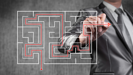 maze game: businessman working on digital screen of maze, business strategy concept