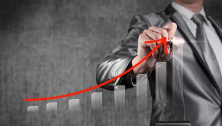 gestion empresarial: Empresario dibujar curva roja con gráfico de barras, concepto de estrategia de negocio Foto de archivo