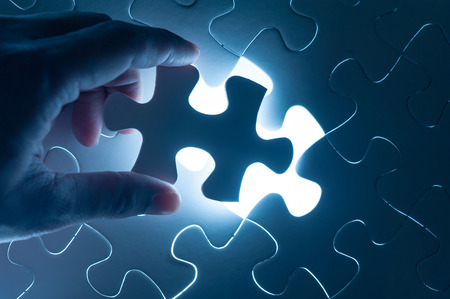 join the team: Hand insert jigsaw, conceptual image of business strategy Stock Photo