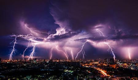 estado del tiempo: Tormenta del relámpago sobre la ciudad en luz púrpura Foto de archivo