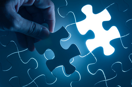 in insert: Hand insert jigsaw, conceptual image of business strategy Stock Photo