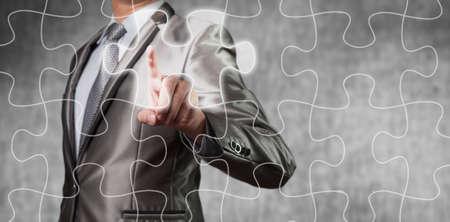 business decision: Businessman using tablet showing jigsaw piece, business decision concept