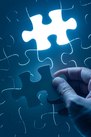 business strategy: Hand insert jigsaw, conceptual image of business strategy Stock Photo