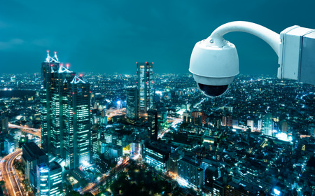 city surveillance: CCTV Camera Operating with city in background