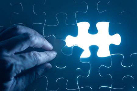 Hand insert jigsaw, conceptual image of business strategy Фото со стока