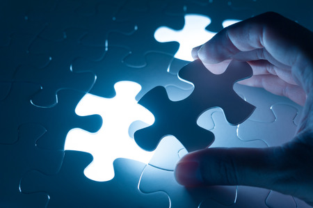 in insert: Hand insert jigsaw, conceptual image of business strategy, decision making concept
