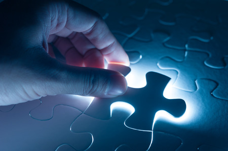 Hand insert jigsaw, conceptual image of business strategy 스톡 콘텐츠
