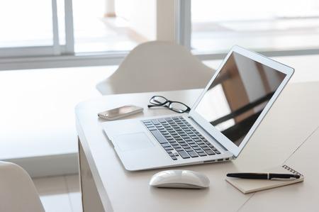 laptop met smartphone en nota boek op bureau