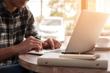 Homme d'affaires utilisant un ordinateur portable avec tablette et le stylet sur la table en bois dans un café avec une tasse de café Banque d'images