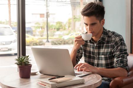 Zakenman met behulp van laptop met tablet en pen op houten tafel in de coffeeshop met een kopje koffie