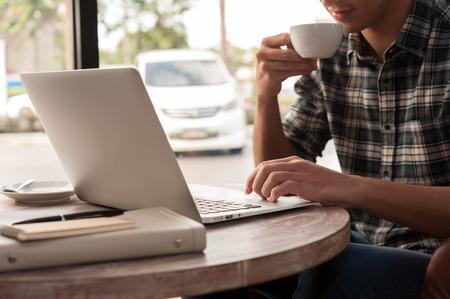 trabajando: Hombre de negocios usando la computadora portátil con la tableta y el lápiz sobre la mesa de madera en la cafetería con una taza de café