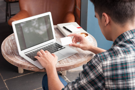 named: Businessman look at named card while using laptop on wooden table in coffee shop