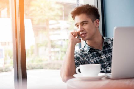handsome men: Uomo d'affari con telefono cellulare mentre portatile lookingat su tavola di legno in caffetteria