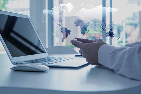 La main en utilisant un téléphone intelligent avec un ordinateur portable, le concept de la mondialisation
