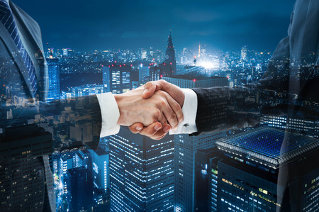 group strength: Business handshake with night scene city in background Stock Photo