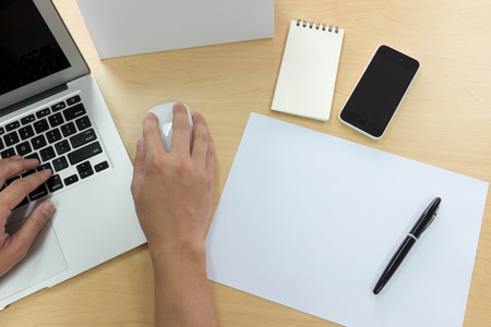 bird eye view: Hands of man using laptop with smart phone, tablet, pen, calendar and a piece of paper Stock Photo