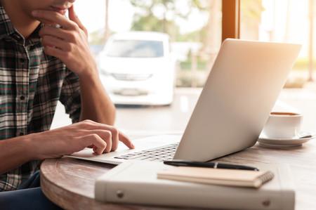 タブレットとペンが一杯のコーヒーのコーヒー ショップで木のテーブルにノート パソコンを使用しての実業家 写真素材