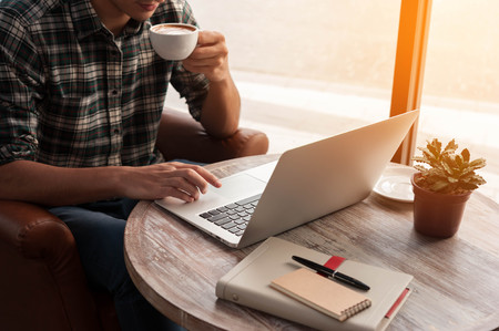 notebook computer: Businessman using laptop with tablet and pen on wooden table in coffee shop with a cup of coffee Stock Photo