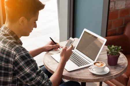 escritura: Negocios usando smartphone y la escritura en la tableta portátil en la mesa de madera en la tienda de café con una taza de café