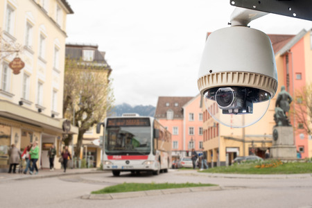city surveillance: CCTV Camera or surveillance technology working on city road Stock Photo