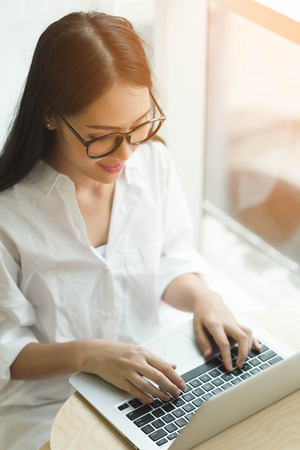 avocation: Woman Using Laptop by the window with sun flare Stock Photo