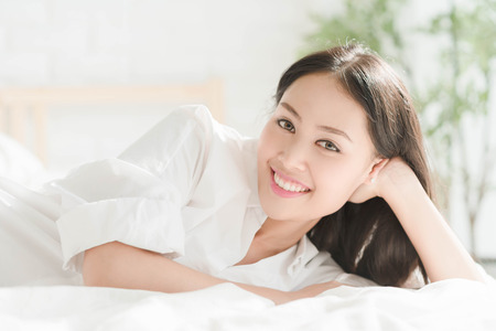 girl lying: Young beautiful girl lying in white bed room Stock Photo