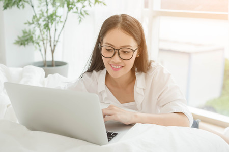 avocation: Woman Using Laptop In Bedroom by the window sit on floor