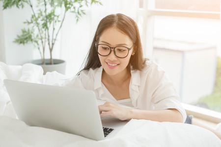 Woman Using Laptop In Bedroom by the window sit on floor