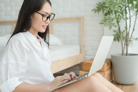 avocation: Woman with eye glasses Using Laptop In Bedroom by the window