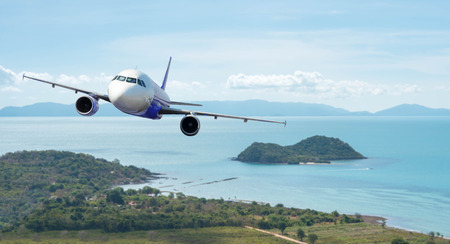Airplane with beautiful ocean and island in background, explore the world Stock Photo