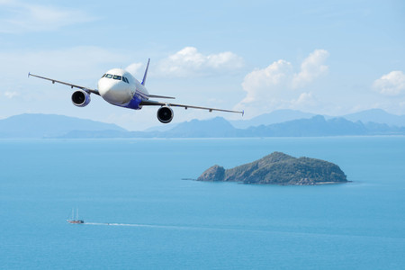 Airplane with beautiful ocean and island in background, explore the world Banco de Imagens