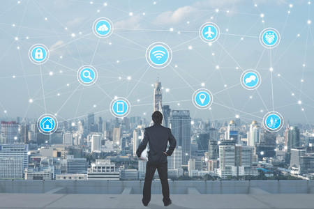 Businessman debout sur le toit de skyscrapper regardant les icônes avec paysage en arrière-plan, Internet des objets conceptuels