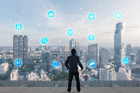 Businessman standing on roof top of skyscrapper looking at icons with cityscape in background, internet of things conceptual