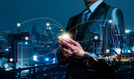Double exposure of business man using smartphone, internet of things conceptual
